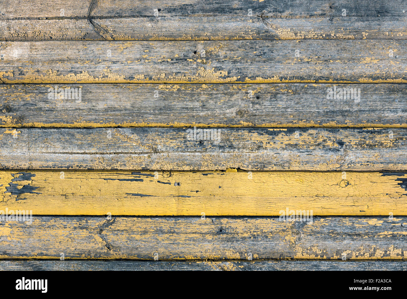 Old wood texture with weathered yellow paint - Stock Image