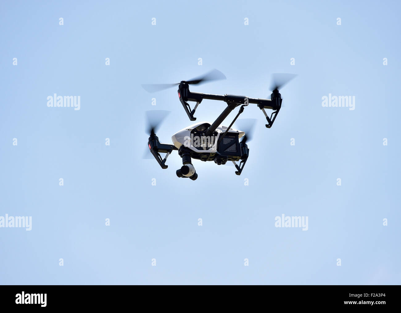 Drone in flight, carrying a film camera - Stock Image