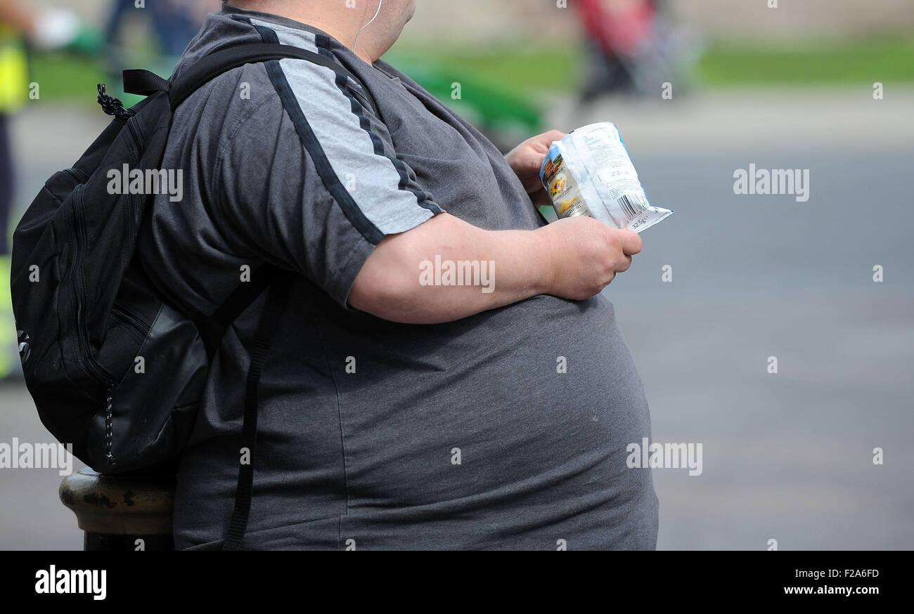 An overweight man eats junk food - Stock Image