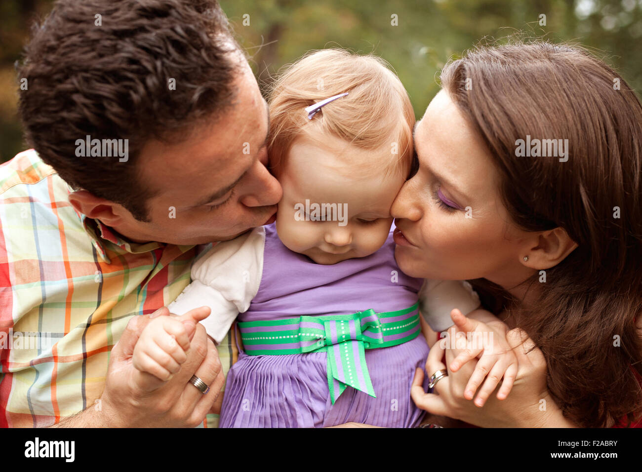 kiss of love - happy parents with their cute baby girl stock photo