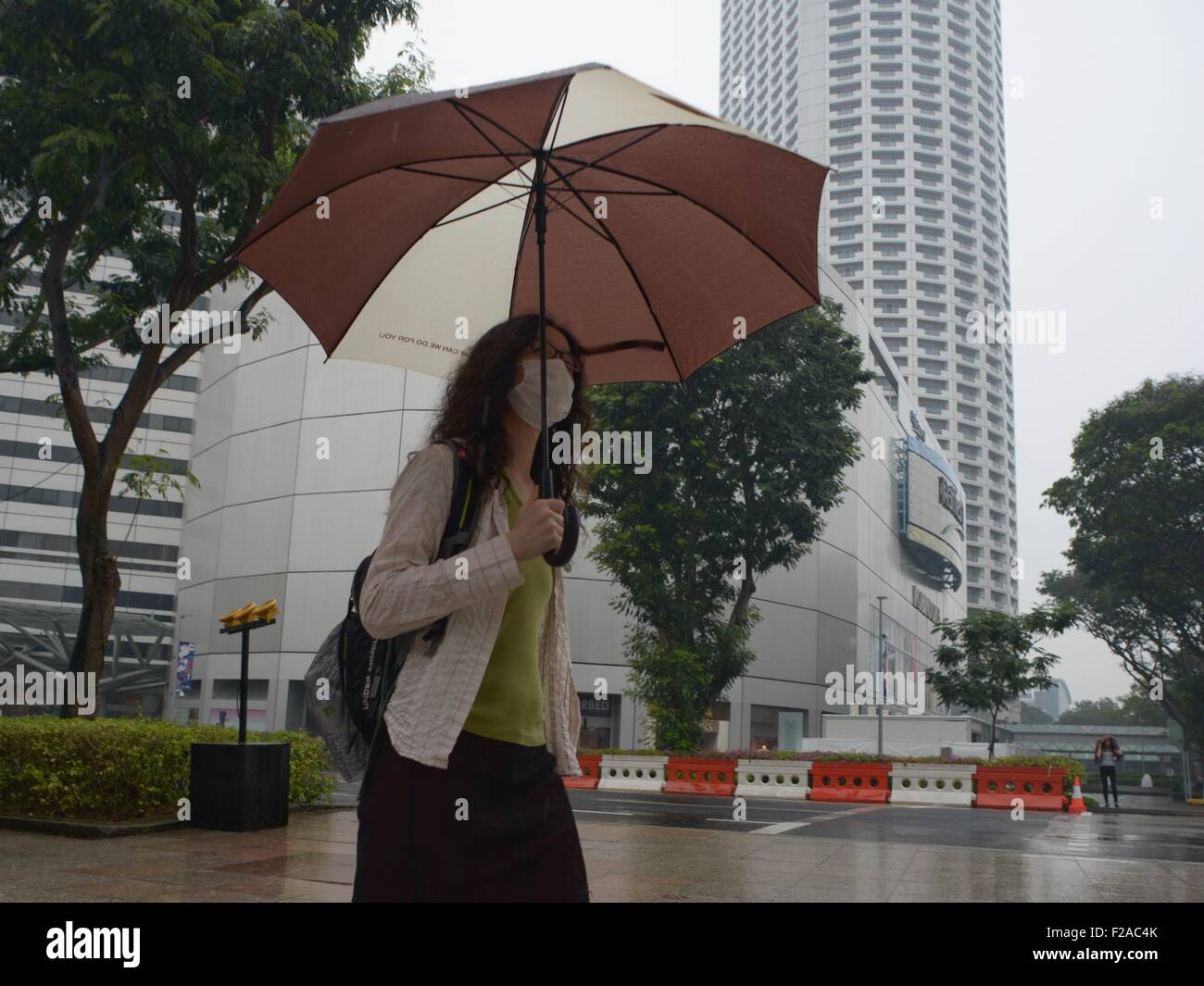 Singapore. 15th Sep, 2015. A woman walks past haze shrouded city centre in the midst of rain in Singapore, Sept. - Stock Image