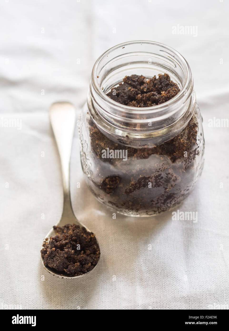 Homemade face and body organic all natural coffee scrub (peeling) in a glass jar placed on a clear background. Spoon - Stock Image