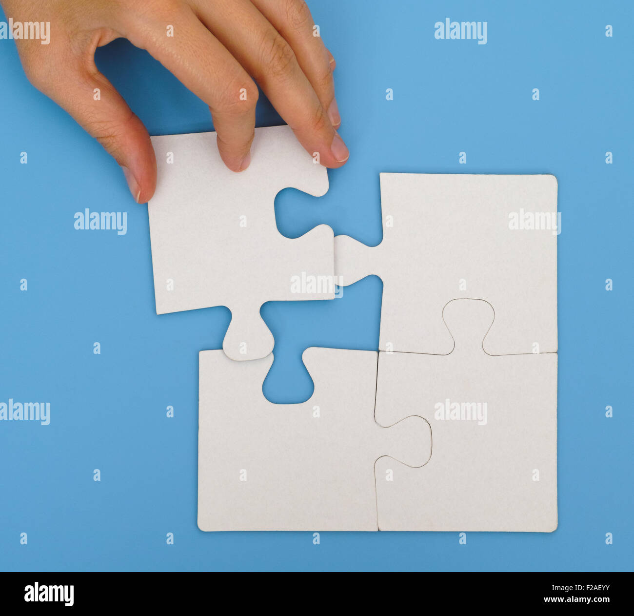 Woman hand putting the final piece to complete simple puzzle on blue background - Stock Image