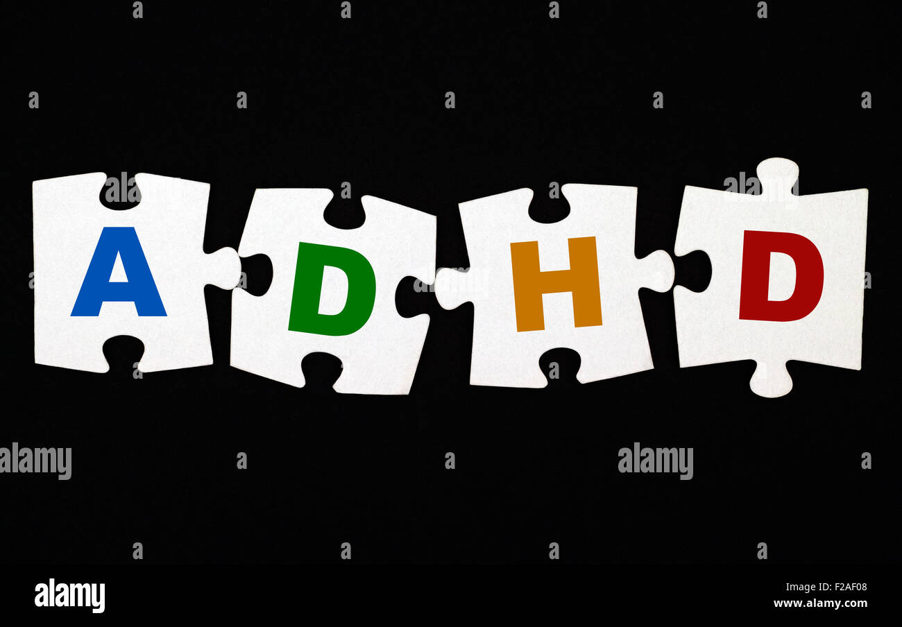 Four pieces of puzzle with letters ADHD on black background. ADHD is Attention deficit hyperactivity disorder. - Stock Image