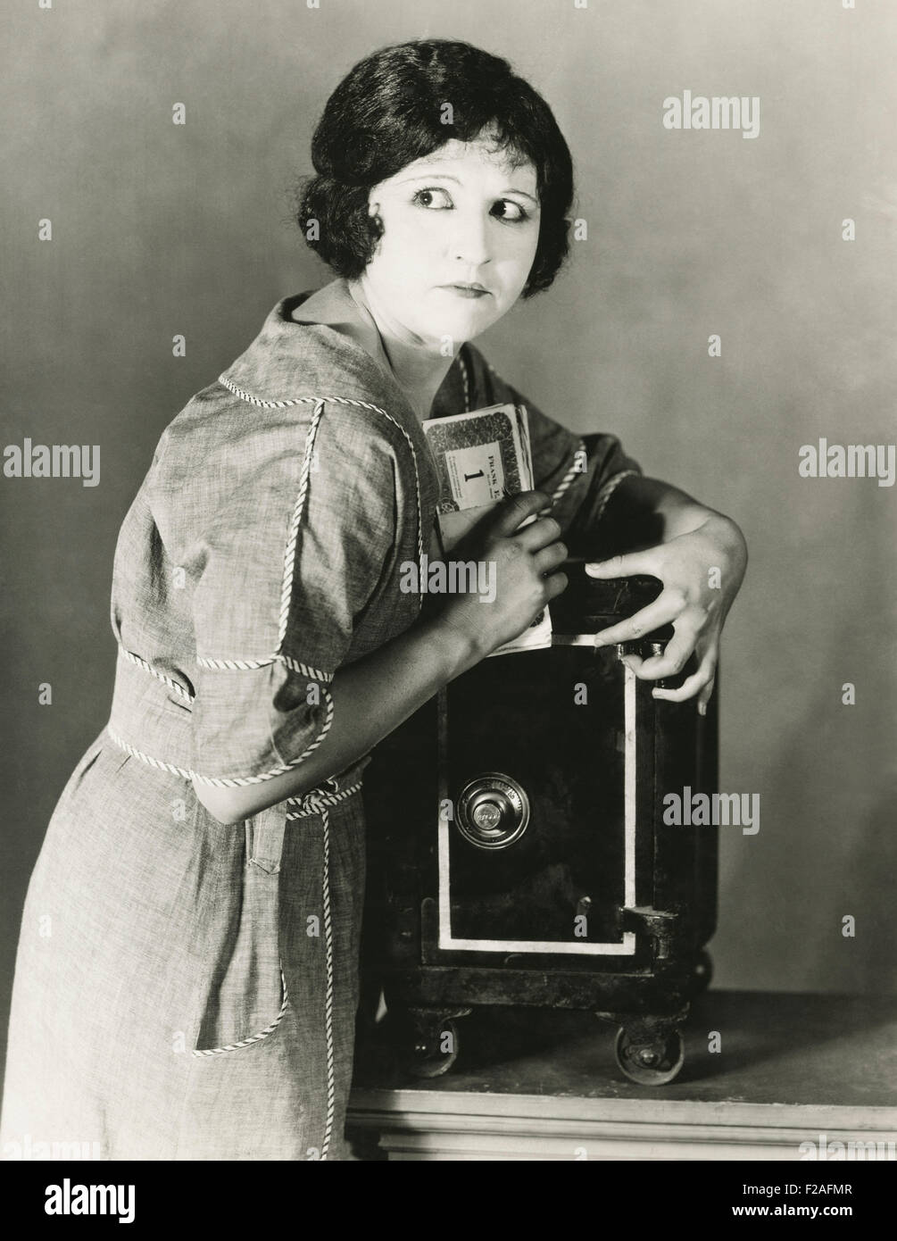 Woman stealing money from safe (OLVI008_OU380_F) - Stock Image