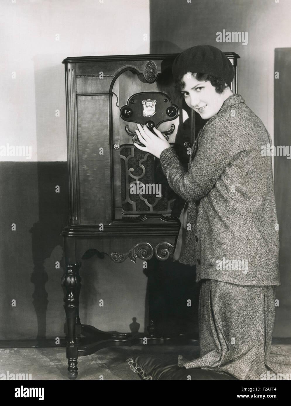 Woman adjusting volume on 1920s radio (OLVI008_OU320_F) - Stock Image