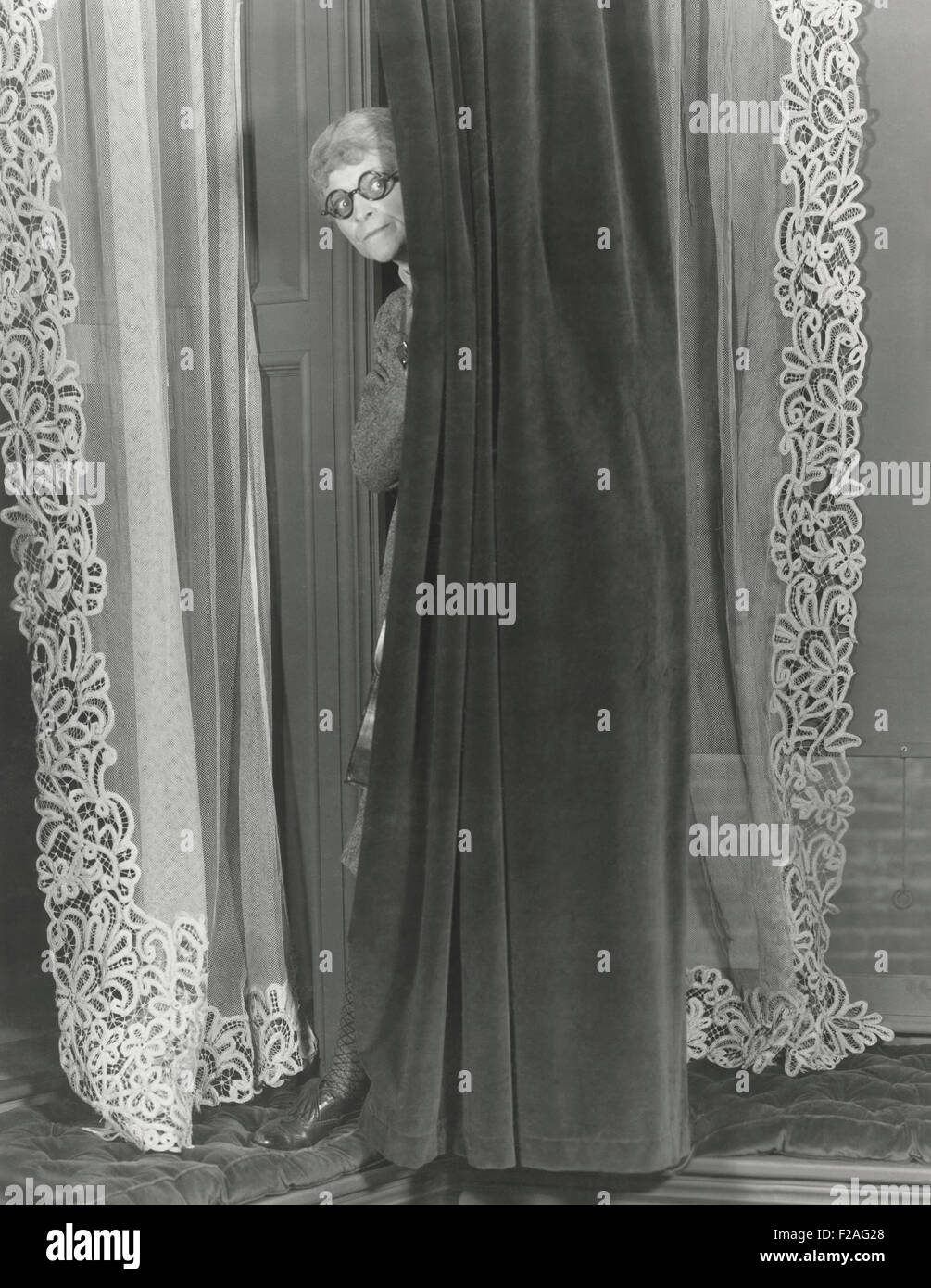 Woman eavesdropping from behind curtain (OLVI008_OU276_F) - Stock Image