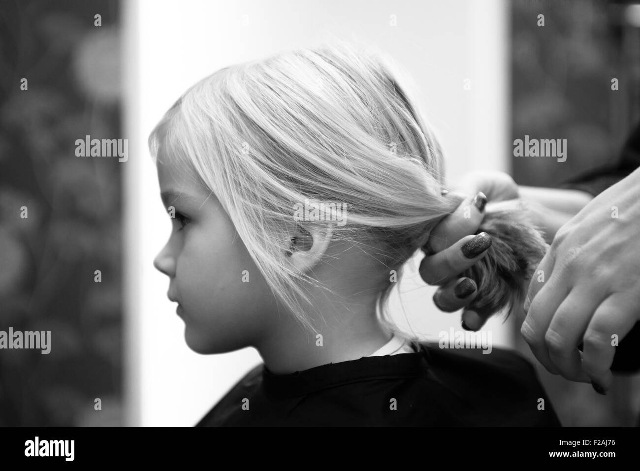 Female hairdresser cutting and brushing young child blond girl hair in hairdressing salon - Stock Image