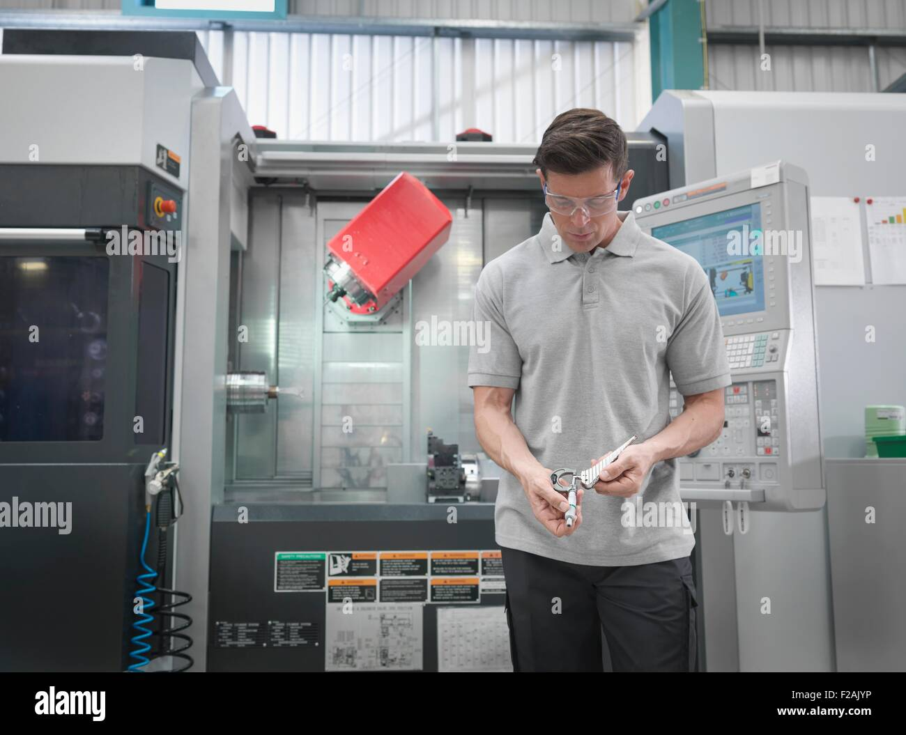 Engineer with CNC lathe making artificial hip joints in orthopaedic factory - Stock Image