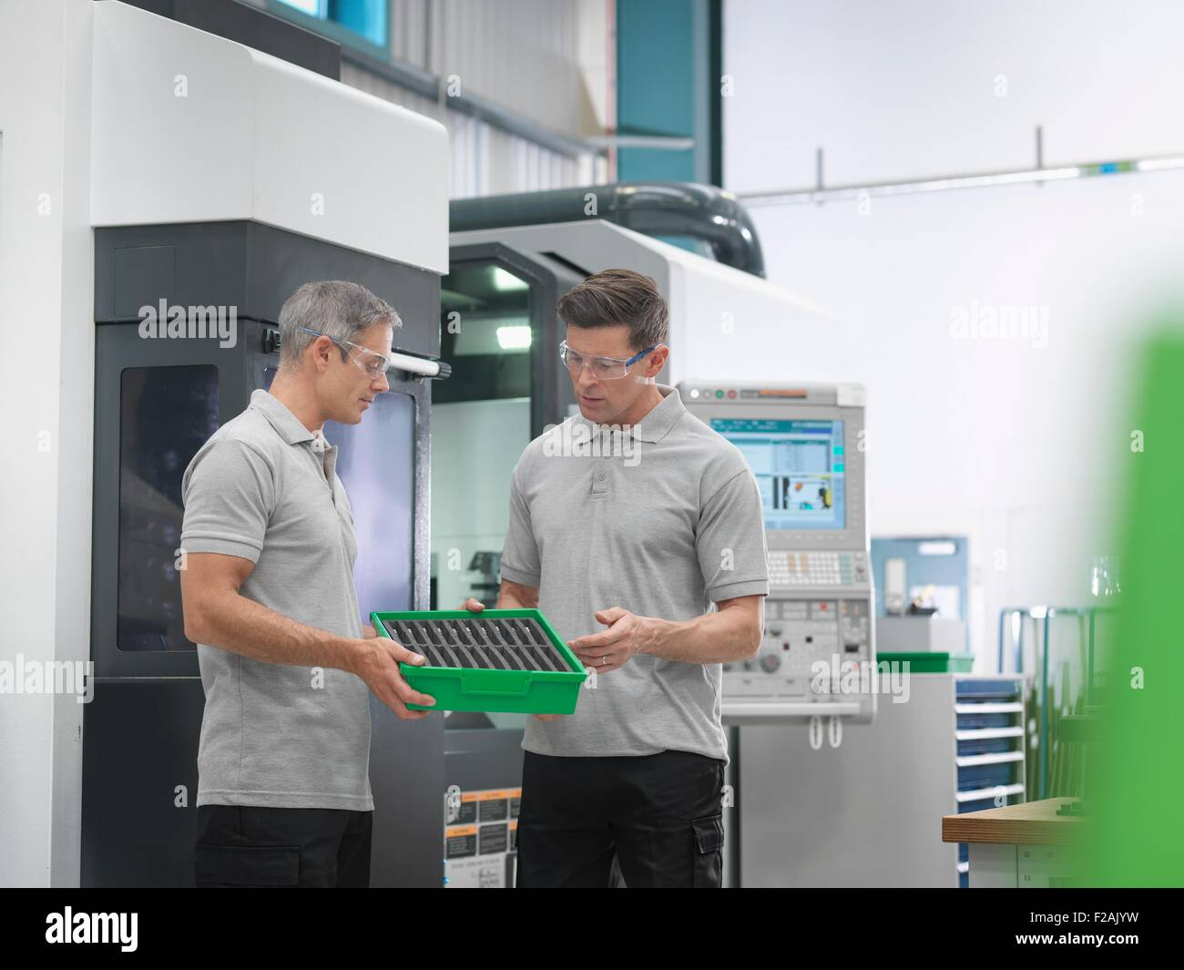 Engineers discussing machined products in orthopaedic factory - Stock Image