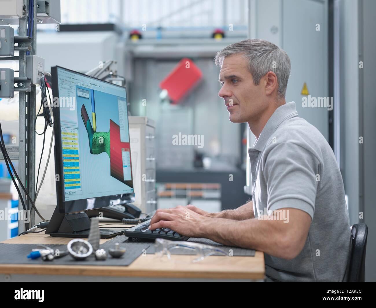 Engineer watching CNC lathe progress on screen in orthopaedic factory - Stock Image