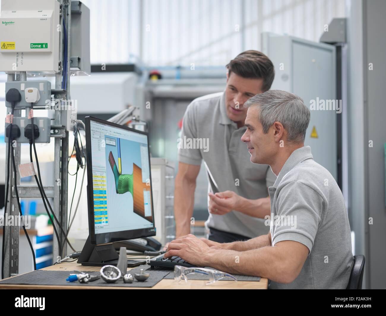 Engineers watching CNC lathe progress on screen in orthopaedic factory - Stock Image