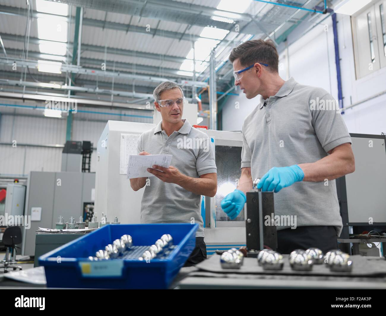 Engineers finishing artificial hip joints in orthopaedic factory - Stock Image