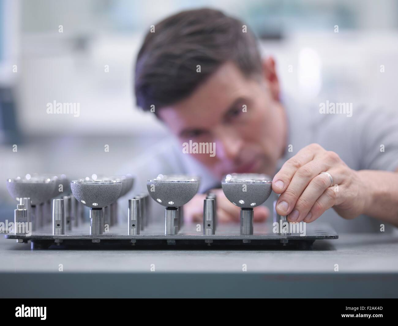 Engineer inspecting artificial hip joint parts in quality control department in orthopaedic factory - Stock Image