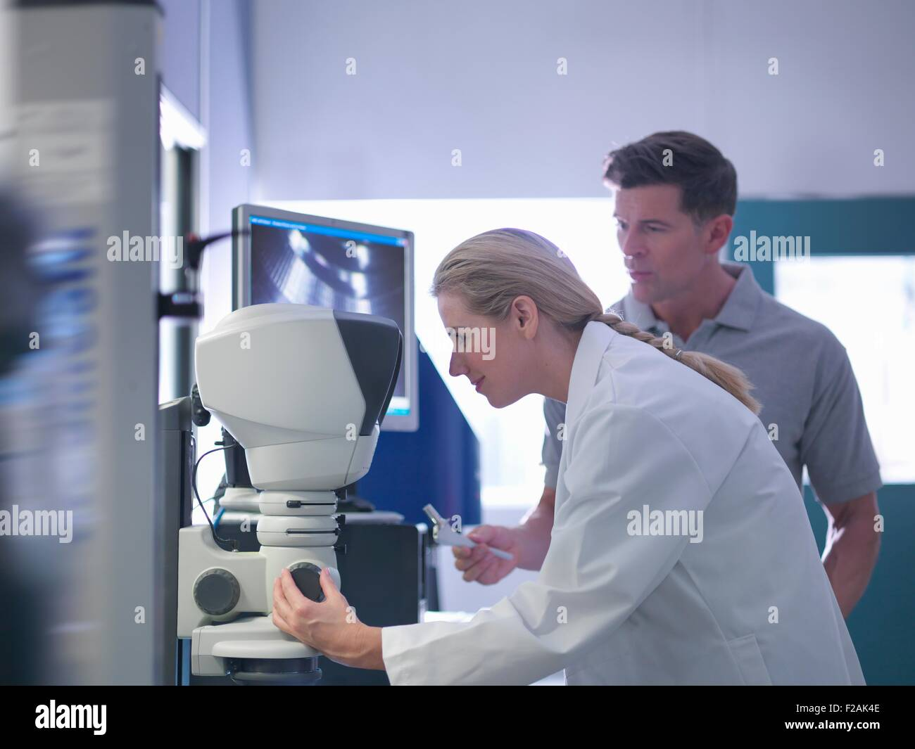 Engineers inspecting artificial hip joint parts using electron microscope in orthopaedic factory - Stock Image