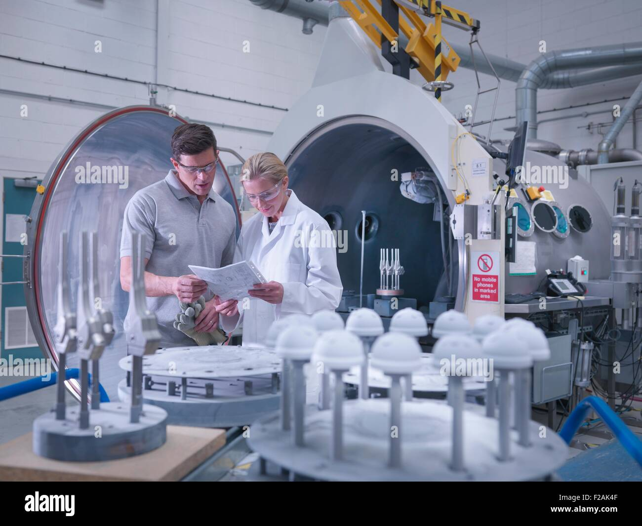Engineers with ceramic coating machine, coating artificial hip joints in orthopaedic factory - Stock Image