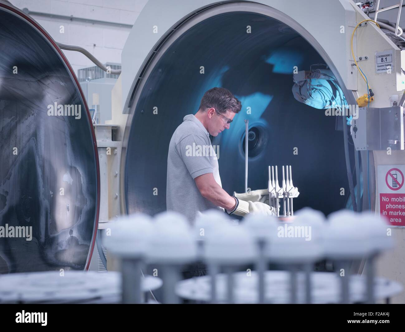 Engineer with ceramic coating machine, coating artificial hip joints in orthopaedic factory - Stock Image