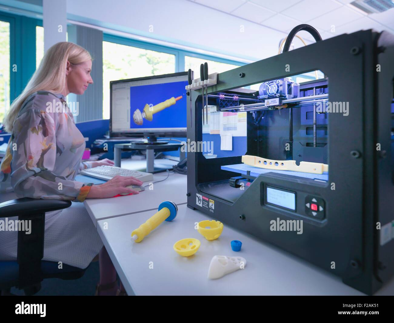 Medical product designer with 3D printing machine with CAD design on screen in orthopaedic factory - Stock Image