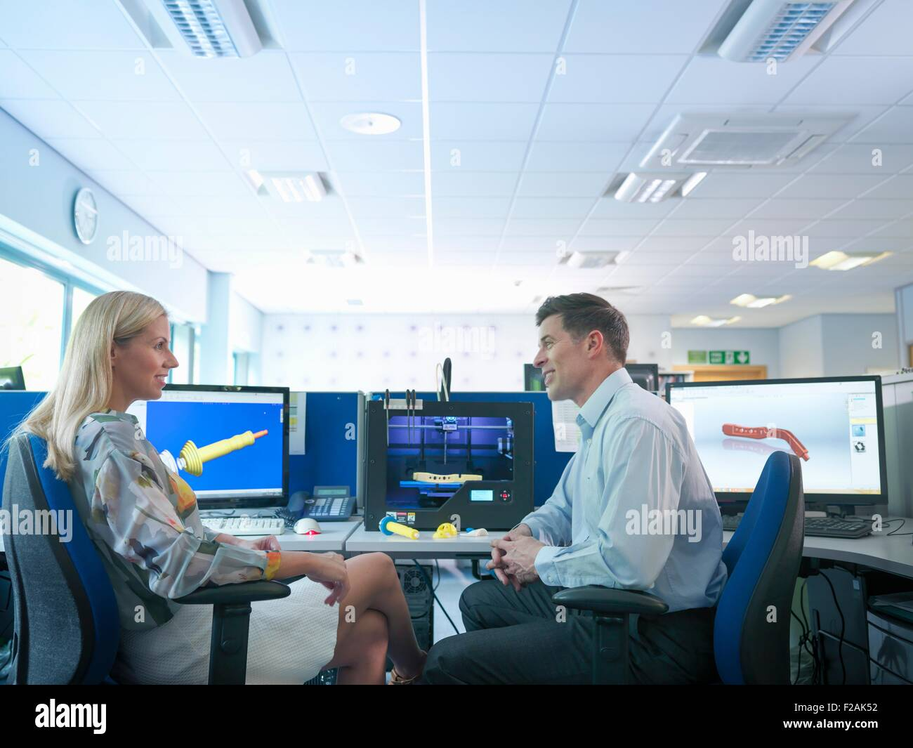 Medical product designers with 3D printing machine with CAD design on screen in orthopaedic factory - Stock Image