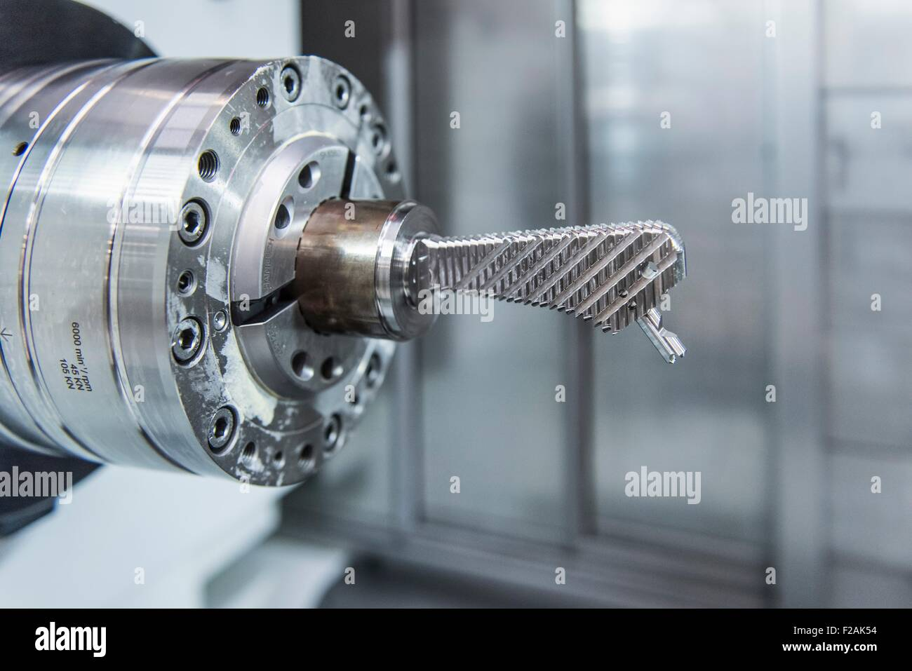 Artificial hip joint in CNC lathe in orthopaedic factory, close up - Stock Image