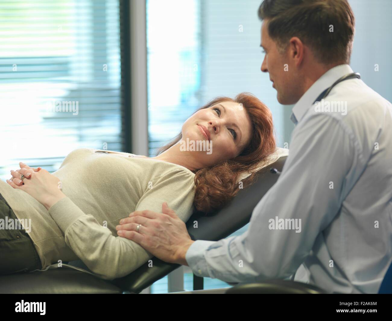 Orthopaedic consultant with patient in consulting room - Stock Image