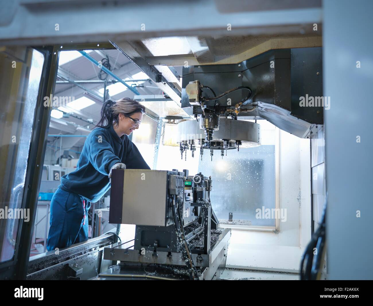 Female apprentice engineer setting up CNC lathe in engineering factory - Stock Image