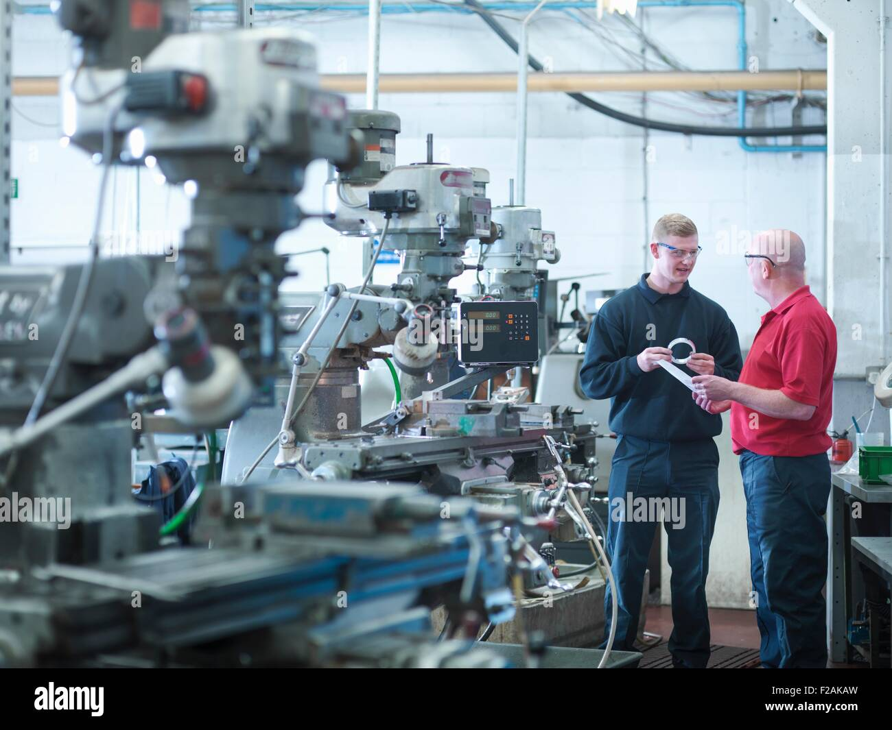 Apprentice engineer with instructor in engineering factory - Stock Image