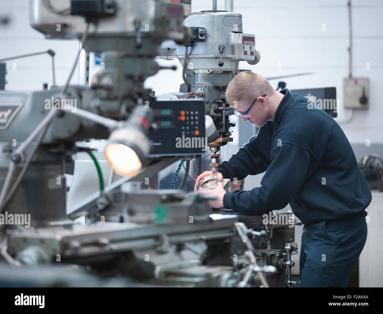 Apprentice engineer on lathe in engineering factory - Stock Image