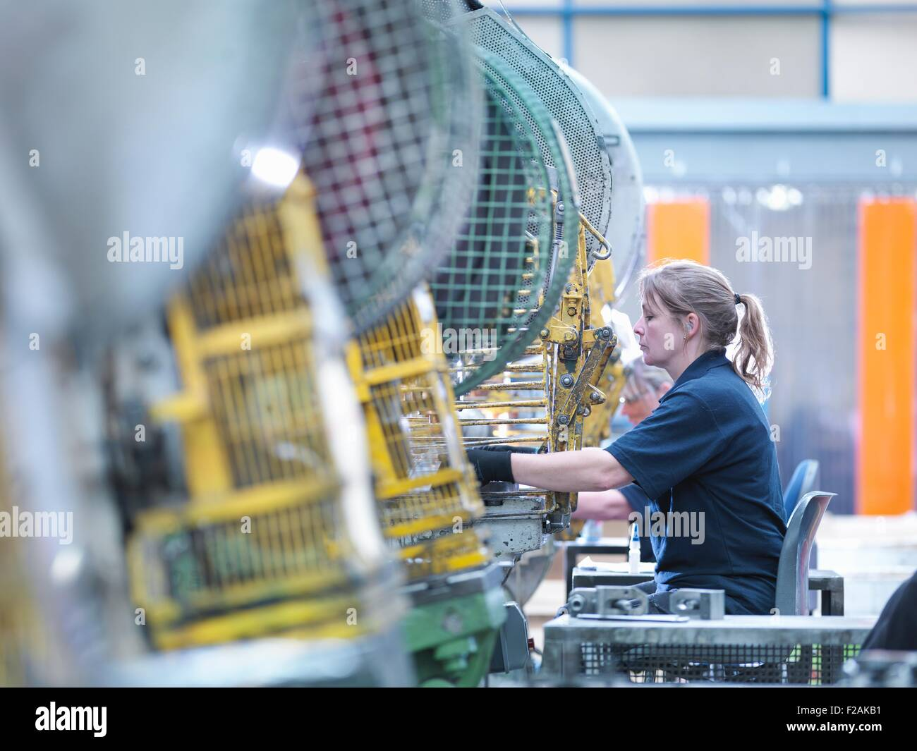 Female worker operating punch machine in engineering factory - Stock Image