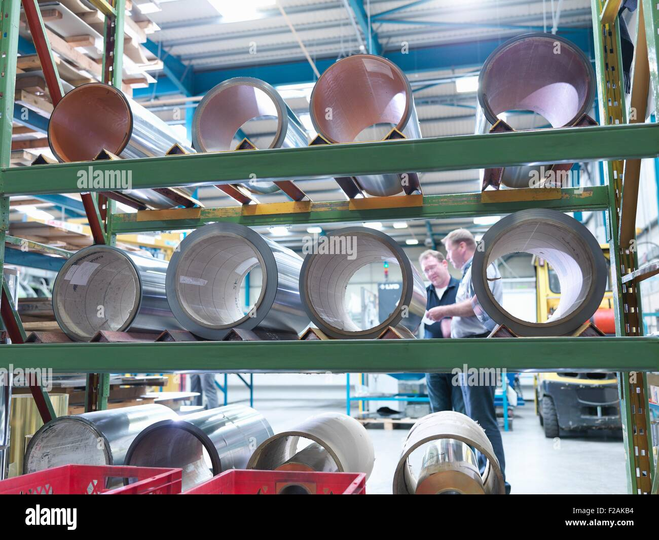 Manager and engineer viewed through rolls of laminated metal in engineering factory - Stock Image