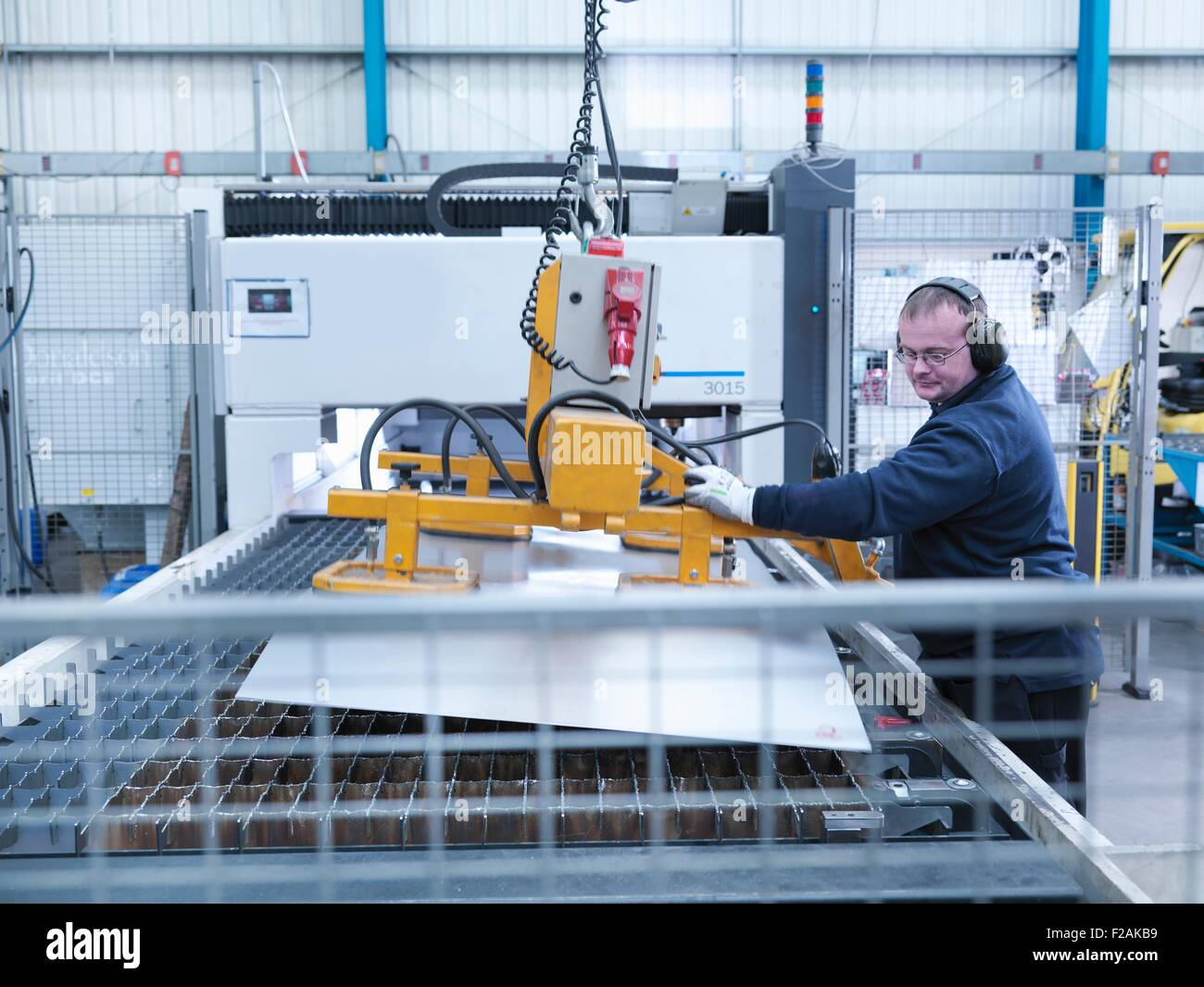 Engineer loading sheet metal into laser cutter in engineering factory - Stock Image