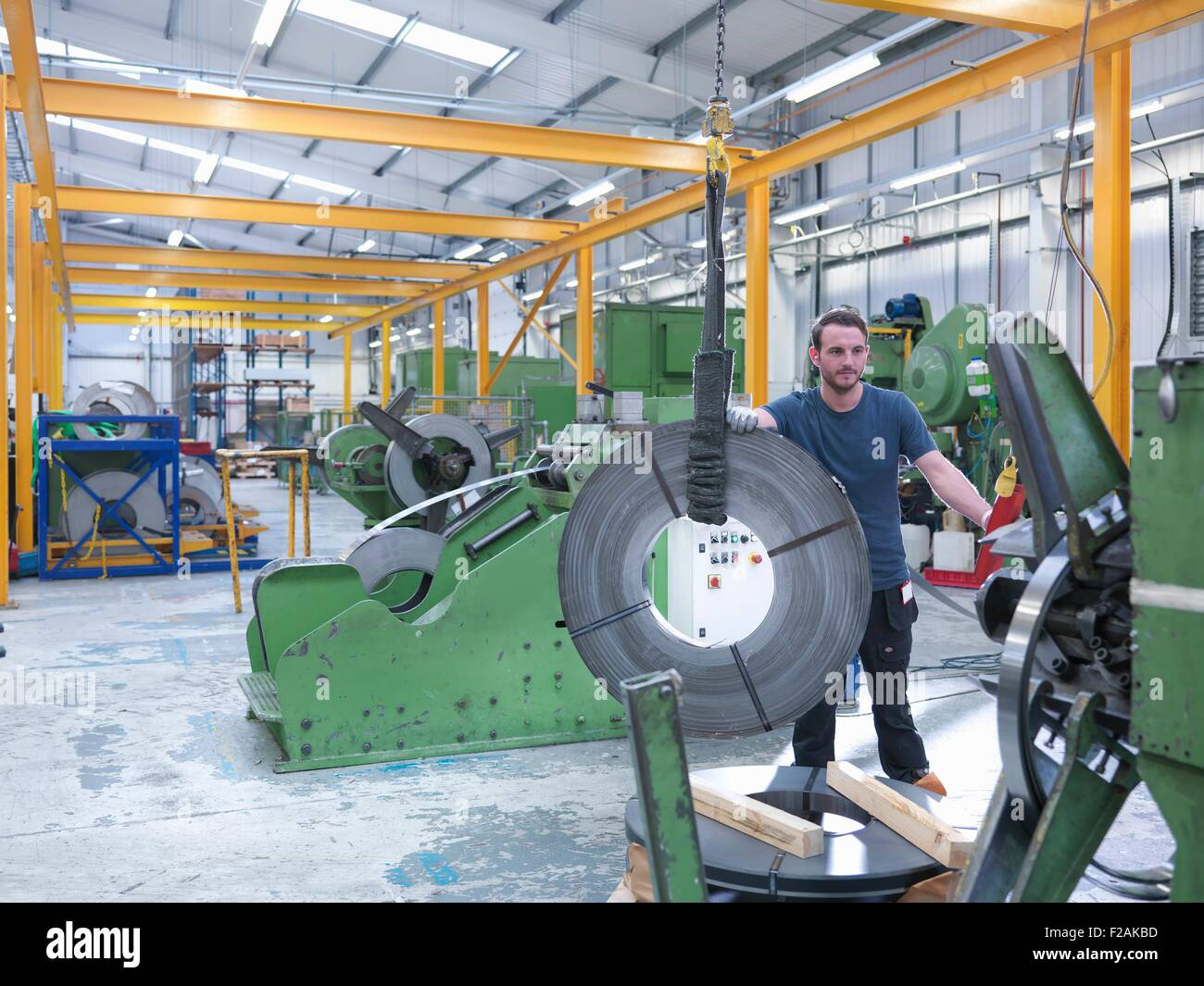 Worker loading rolls of metal into stamping machine in engineering factory - Stock Image