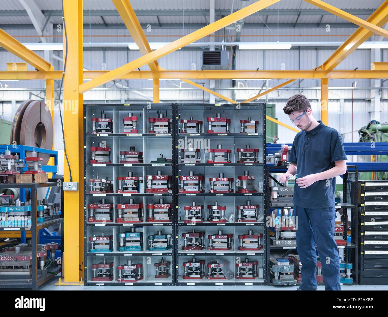 Apprentice engineer with engineering tools in engineering factory - Stock Image