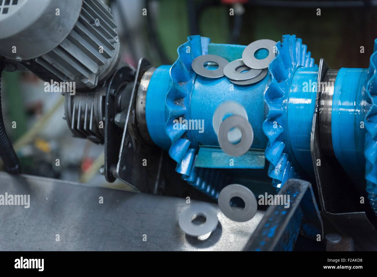 Cut metal washers on machine in engineering factory, close up - Stock Image