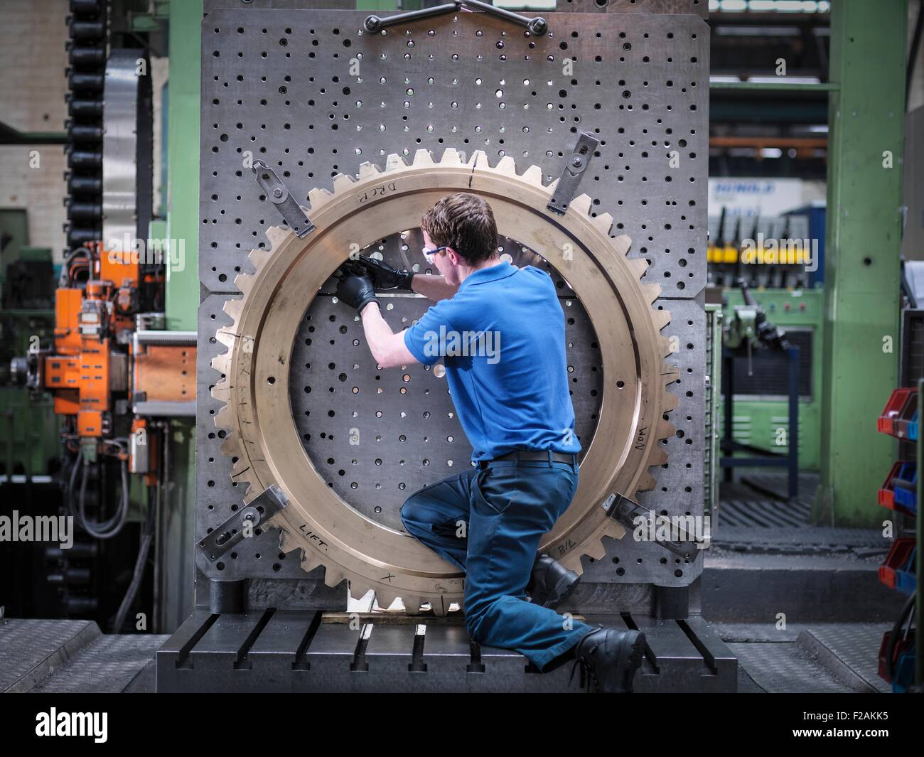 Engineer fitting gear wheel on lathe in engineering factory - Stock Image