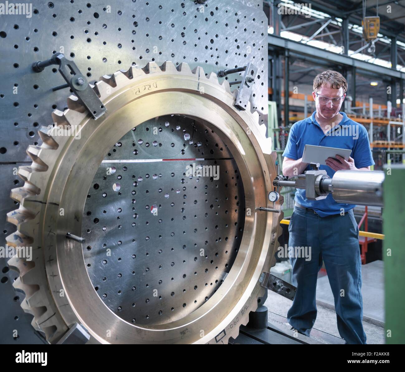 Engineer inspecting drawing on digital tablet of gear wheel on lathe in engineering factory - Stock Image