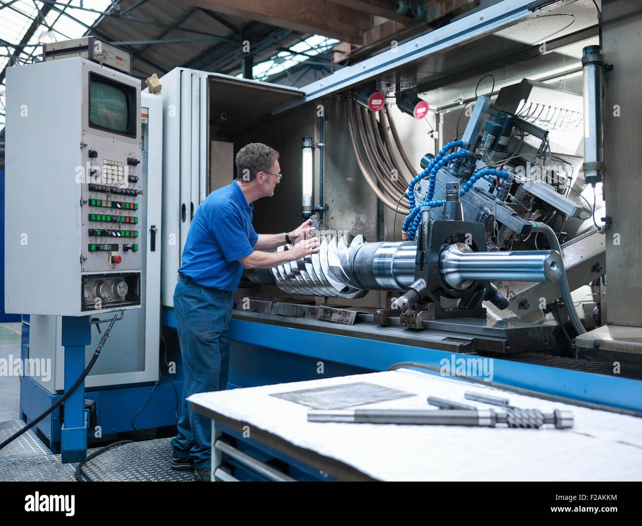 Engineer inspecting worm drive gear in lathe in engineering factory - Stock Image