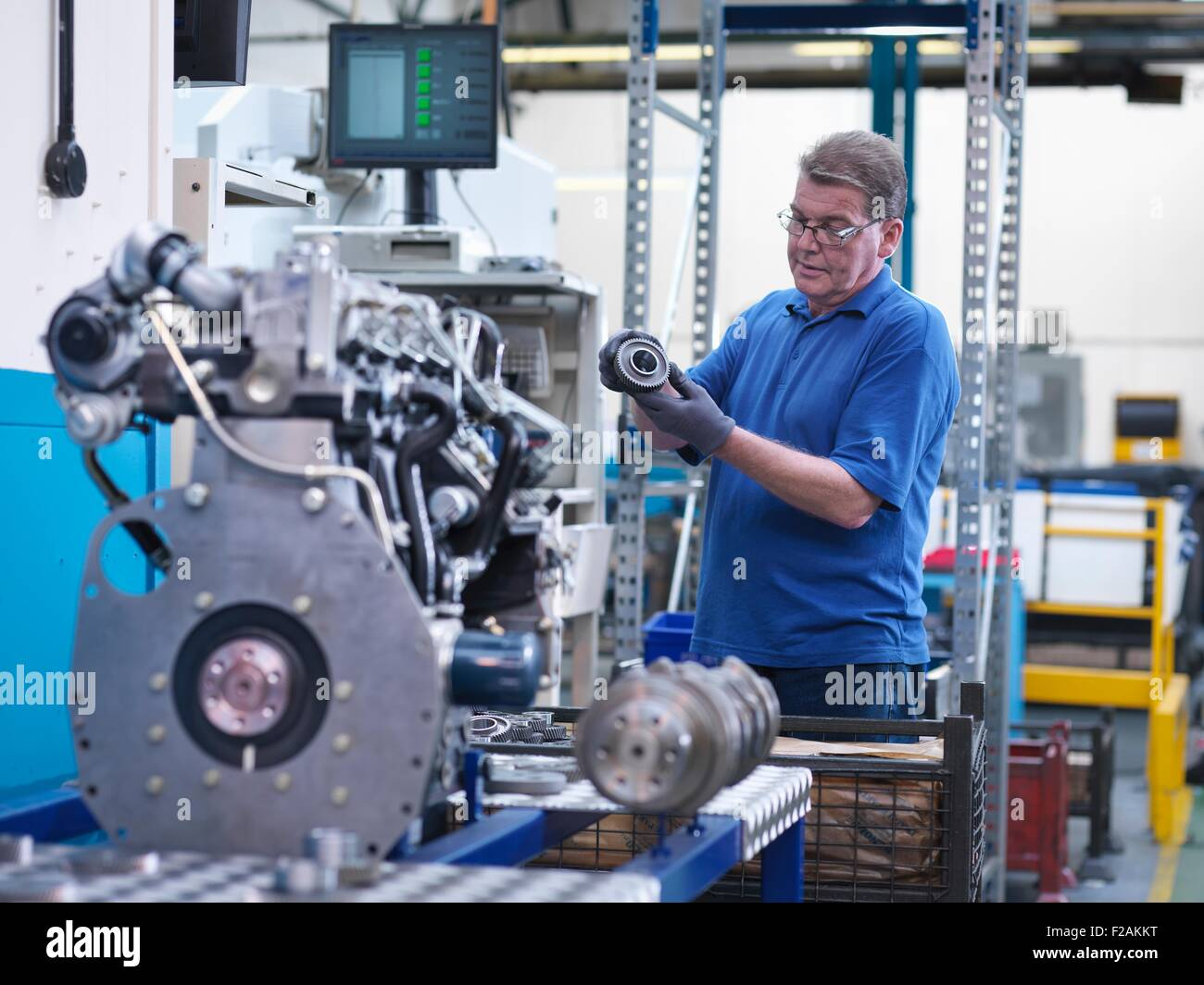 Engineer with gear wheel and diesel engine in engineering factory - Stock Image