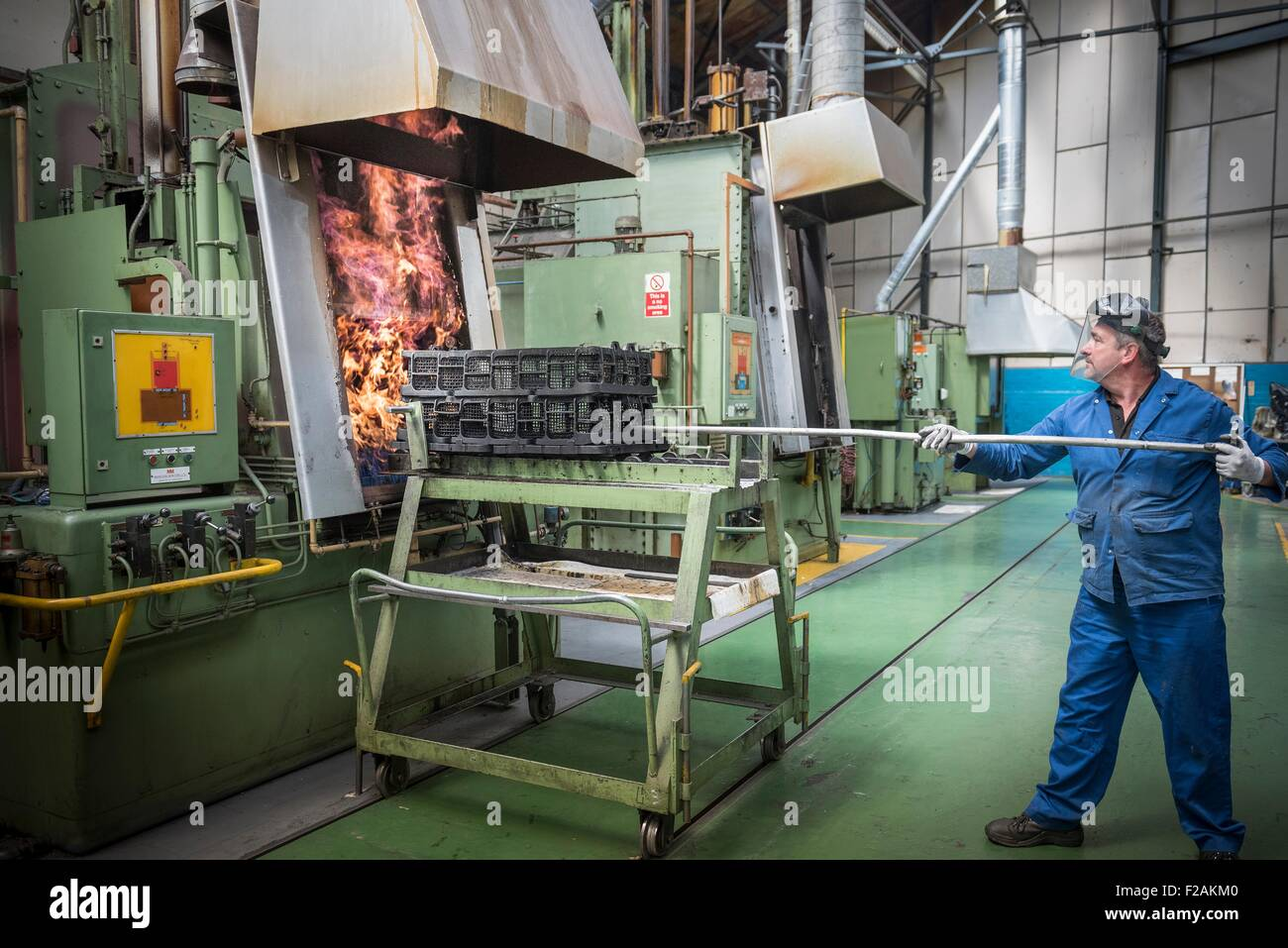 Engineer heat treating gear wheels in engineering factory - Stock Image