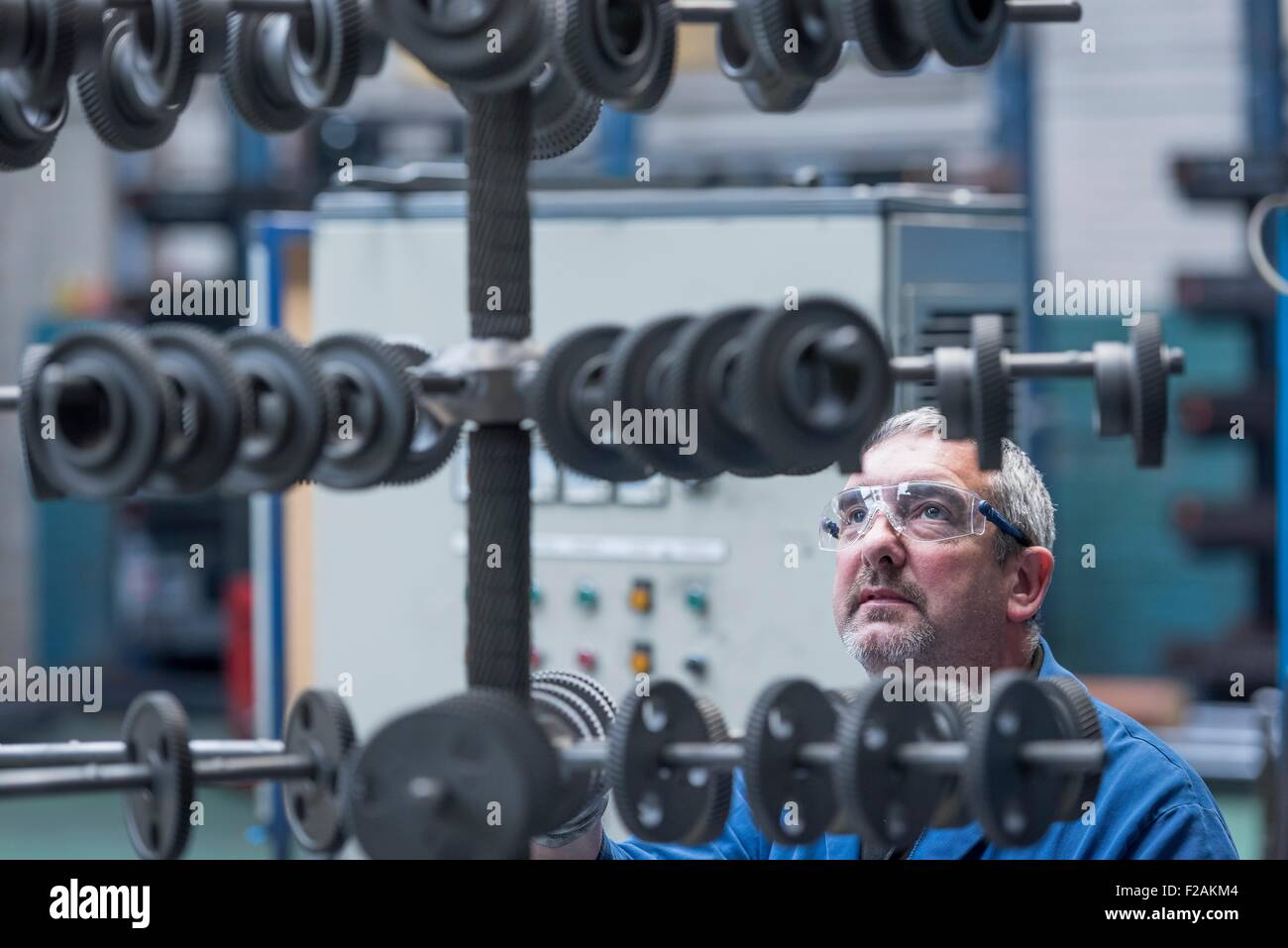 Engineer with shot blasted gear wheels in engineering factory - Stock Image