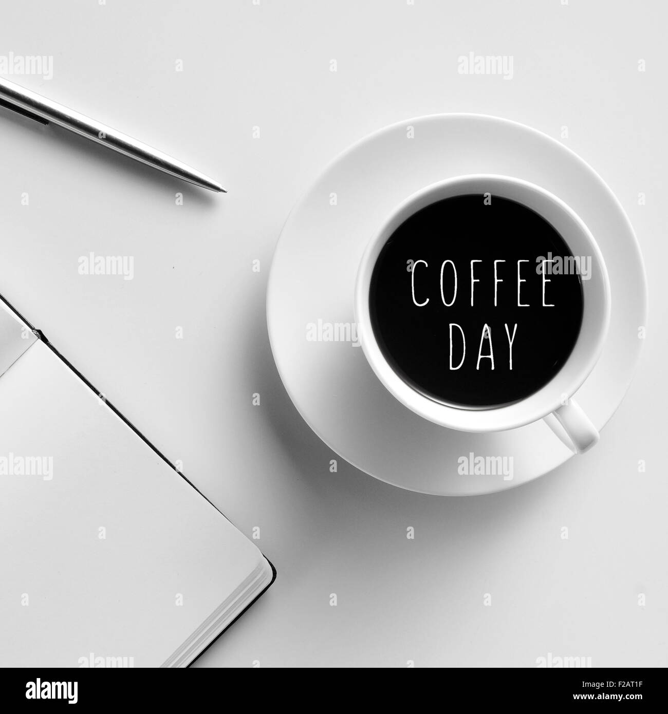 high-angle shot of a white table with a notepad, a pen and a cup of coffee with the text coffee day written in it - Stock Image