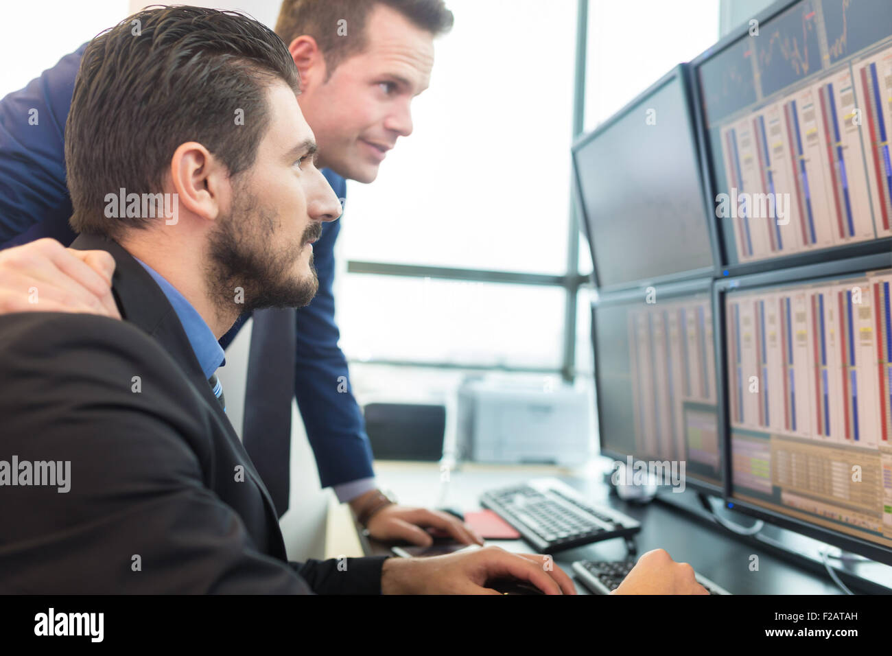 Stock traders looking at computer screens. - Stock Image