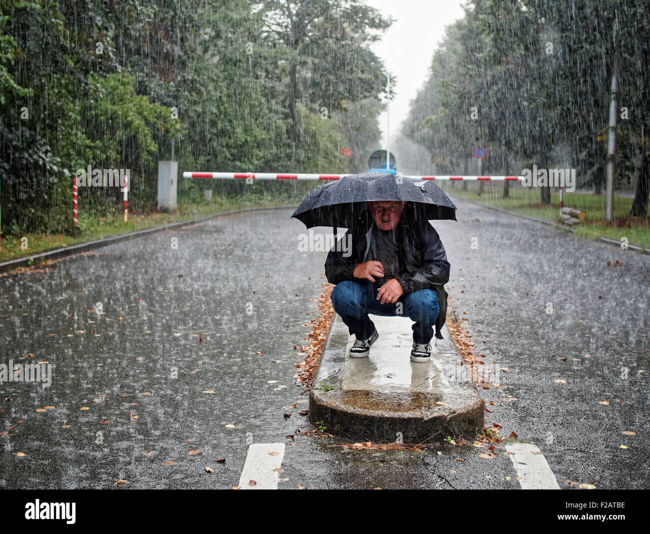 Male crouching under umbrella on a rainy day - Stock Image