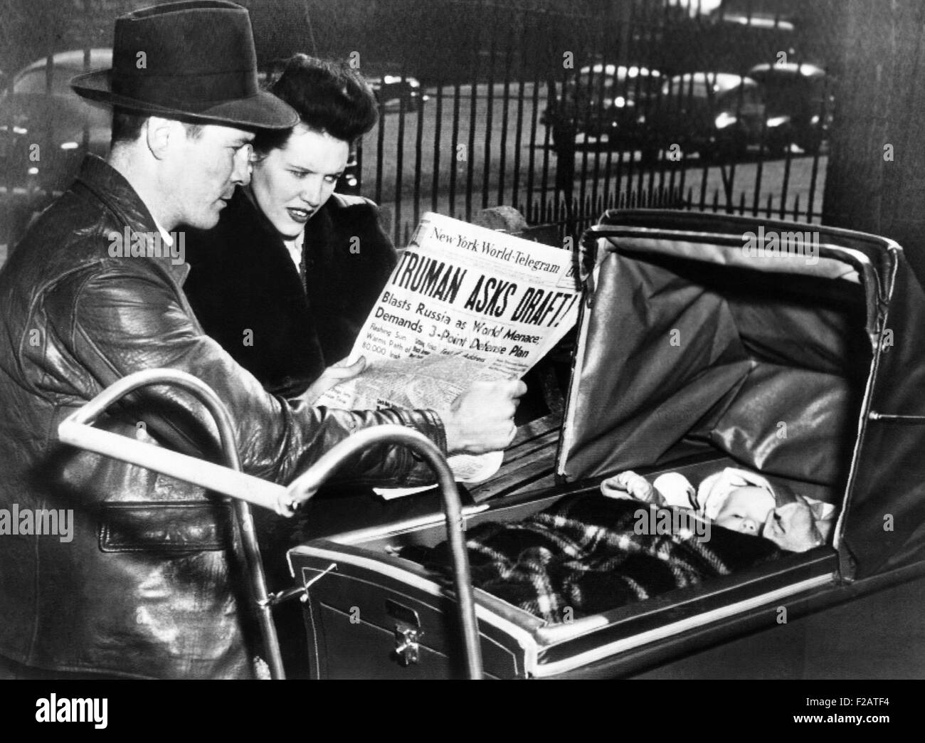 A World War II veteran and his wife, with baby, read headline, 'Truman Asks Draft!' March 17, 1948. In response - Stock Image