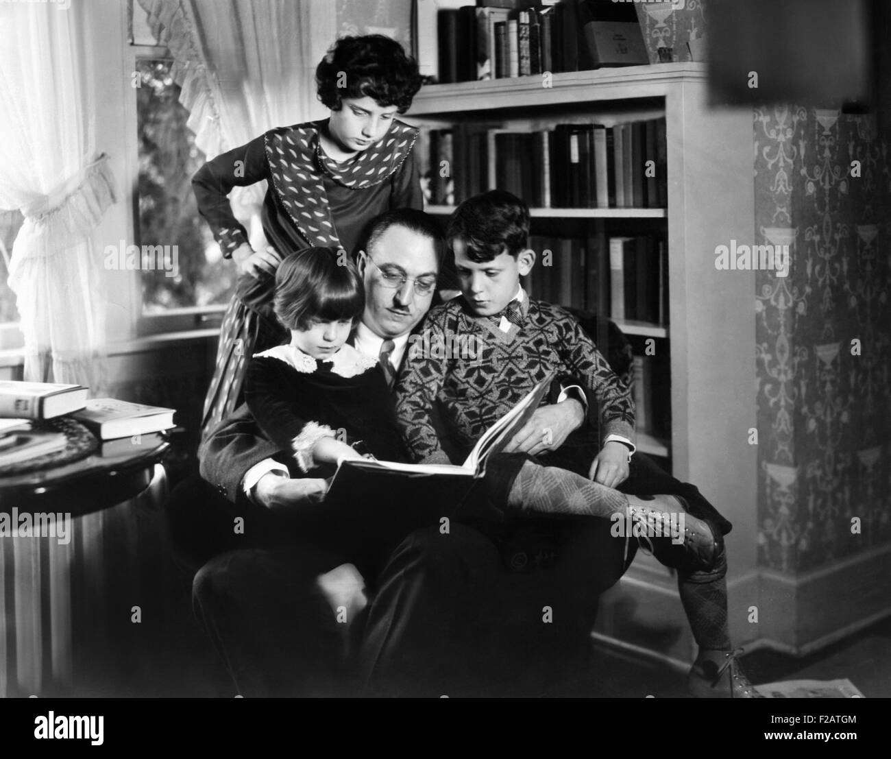 Dr. Karl A. Menninger, psychiatrist, with his children. Ca. 1930. They are playing anagrams. Julia is standing, - Stock Image