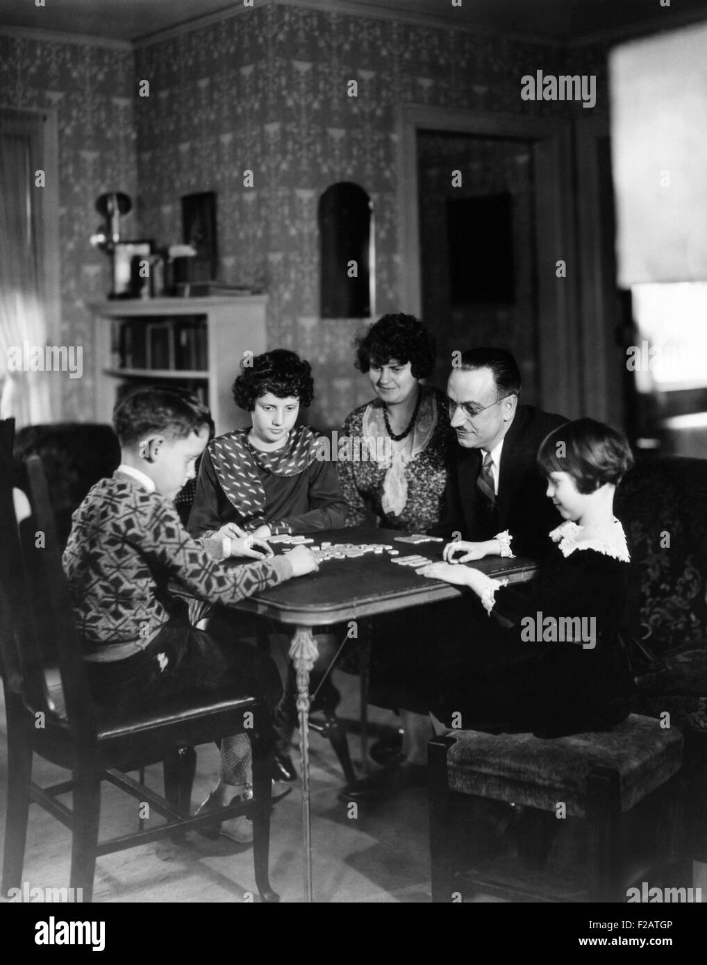 Dr. Karl A. Menninger, psychiatrist, playing a game with his family. Ca. 1930. L-R: Robert Gaines, Julia, Mrs. Menninger, - Stock Image