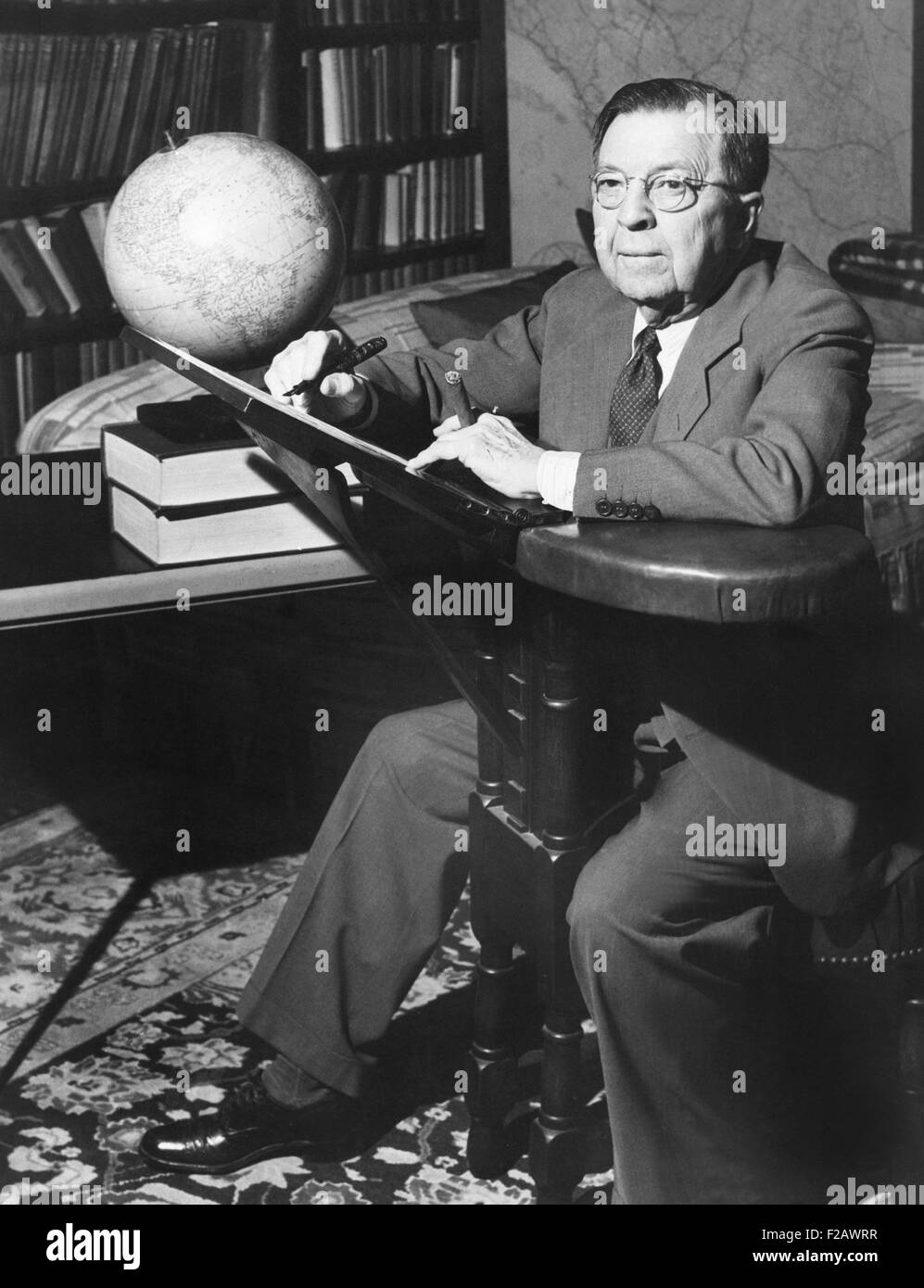 NBC Radio commentator Rupert Hughes at his unique 'writing chair'. May 1943. He named it 'Hughes Folly', - Stock Image
