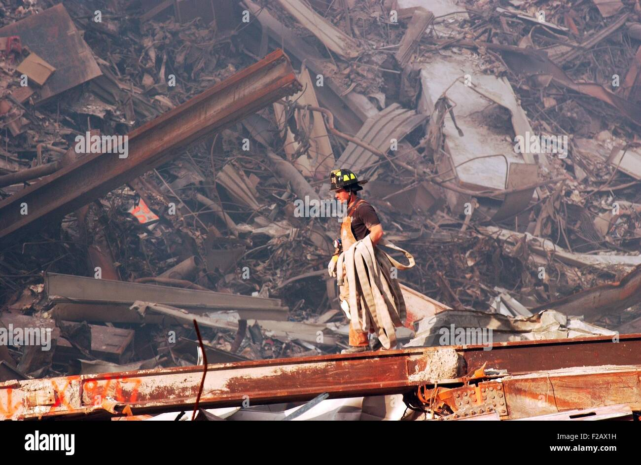 NYC Fire fighter carries a fire hose over smouldering fires and wreckage at Ground Zero, Sept. 18, 2001. World Trade - Stock Image