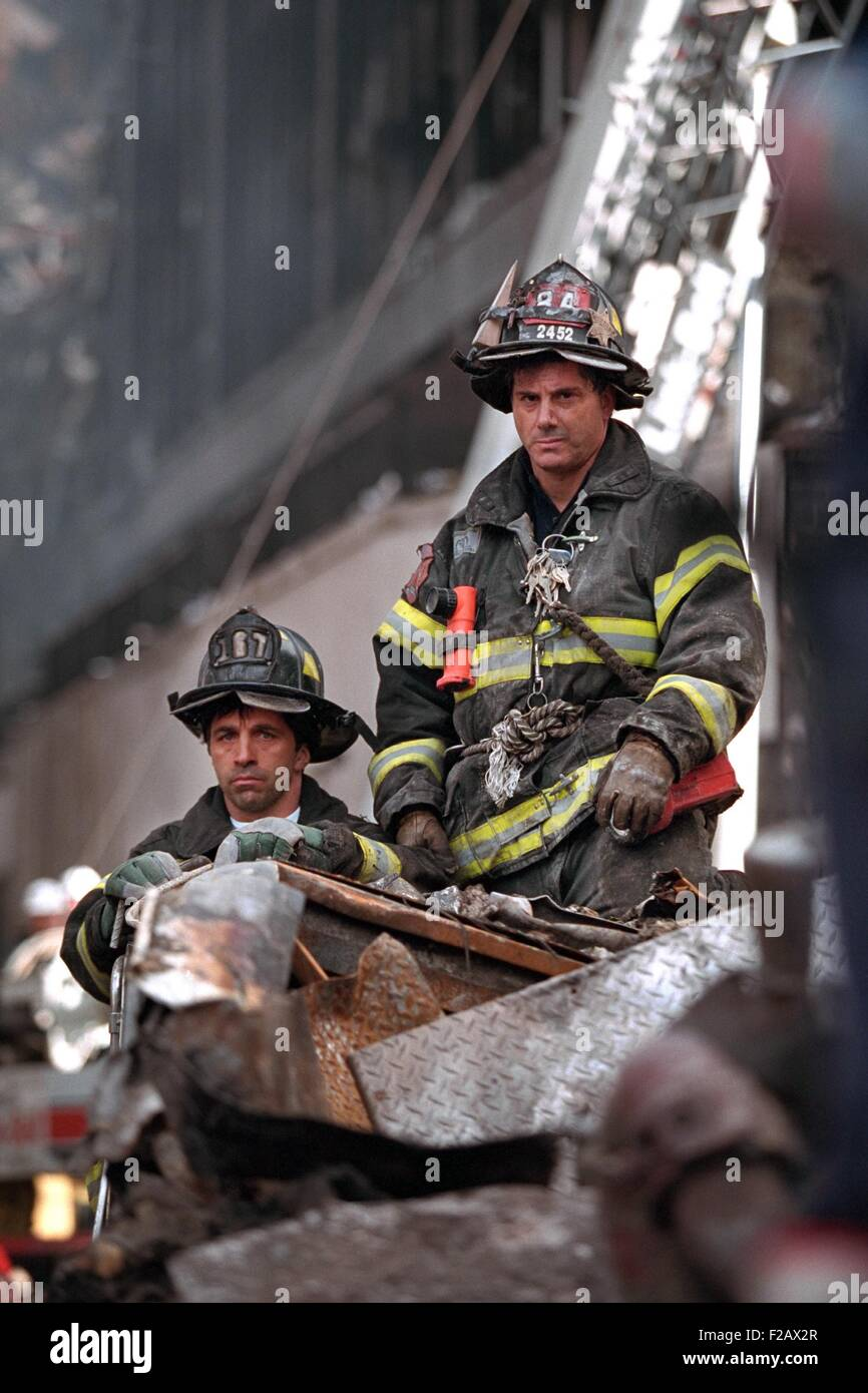 NYC Firemen, grim and geared for rescue/recovery work at the destroyed World Trade Center, NYC. They have a high - Stock Image