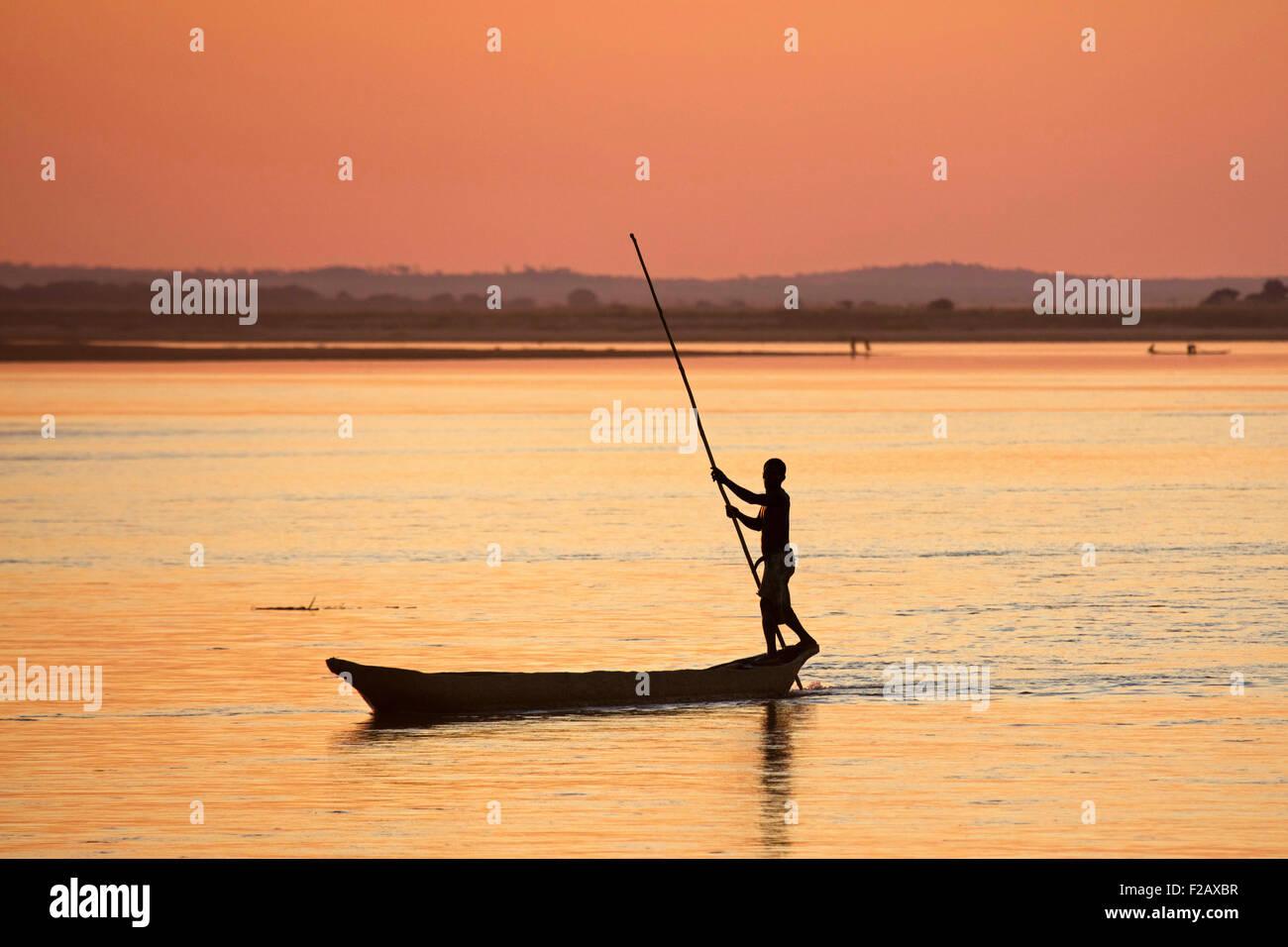 Silhouette of Malagasy fisherman punting pirogue with push pole on Tsiribihina / Tsiribinha river at sunset, Menabe, - Stock Image
